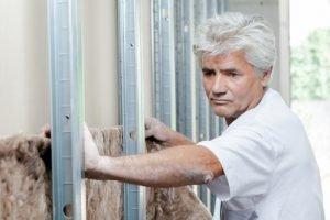 Installing fibreglass insulation and blue
