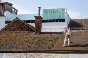 man cleans roof